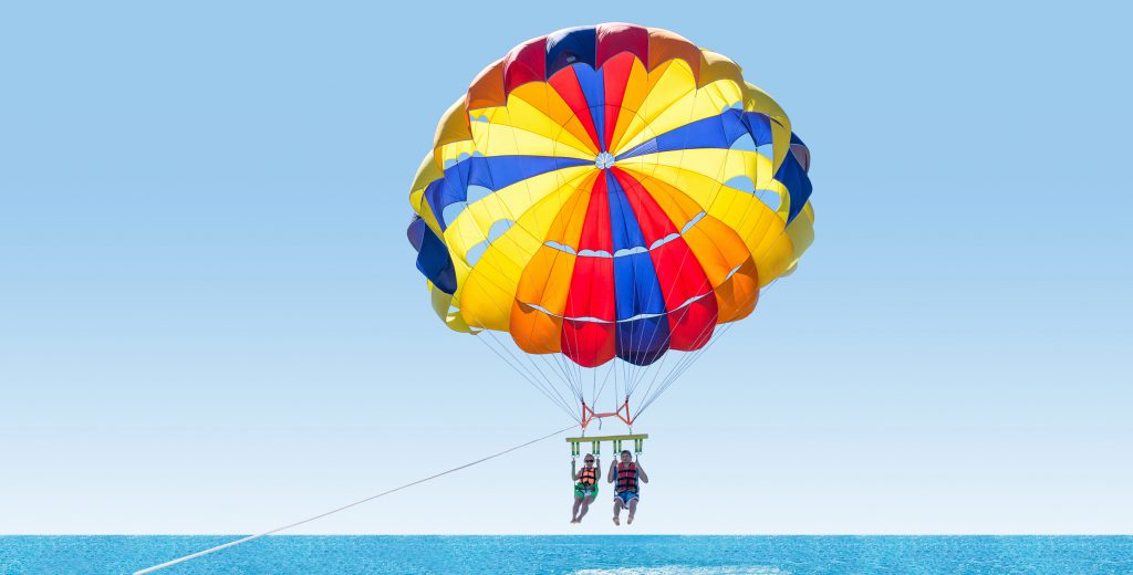 couple parasailing on a beach