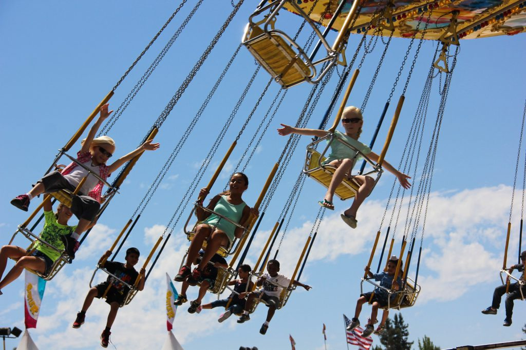 people on swings ride in the air with clouds and blue sky