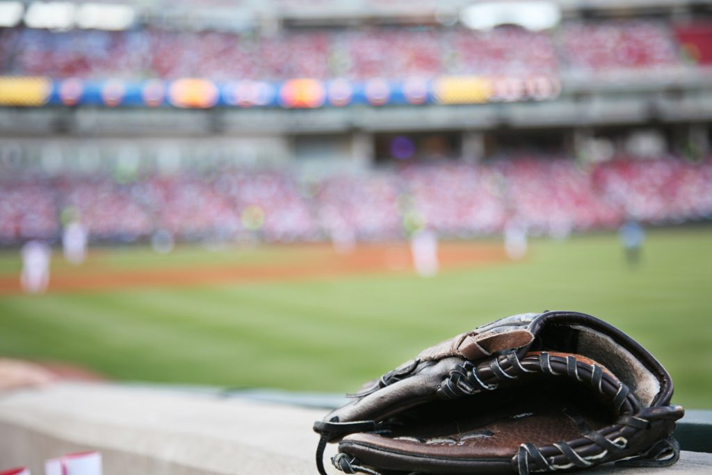 Baseball glove on the wall with a minor league stadium in the background