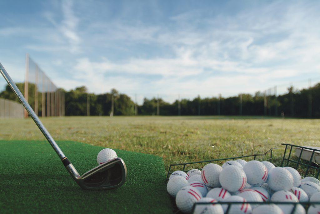 basket of golf balls, golf club, grass
